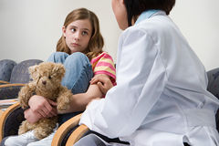 Doctor comforting nervous girl Royalty Free Stock Photos