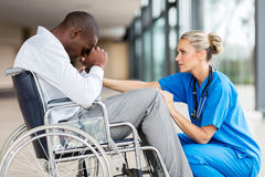 Doctor comforting patient. Caring middle aged doctor comforting a disabled patient royalty free stock photo