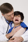 Doctor comforting a scared little boy Stock Images