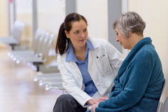 Doctor comforting senior patient Stock Images