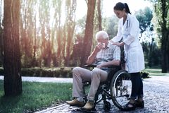 Doctor comforts the crying old man in the summer park. The doctor comforts the crying old men who sits in a wheelchair in the summer park stock photography