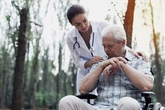 Doctor comforts the sad old man. Doctor comforts a brooding, sad old men sitting in a wheelchair in the park royalty free stock photography