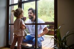 Free Doctor Coming To See Family In Isolation, Window Glass Separating Them. Royalty Free Stock Photo - 184074075