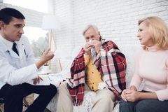The doctor communicates with the old man`s wife, who sits next to him and blows his nose. A doctor came to the old men in a yellow cardigan. The doctor royalty free stock photo