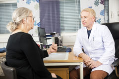 Doctor Communicating With Senior Female Patient At Desk. Male doctor communicating with senior female patient at desk in office stock image