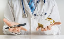 Doctor is comparing conventional tobacco cigarettes and electronic vaporizer Stock Photo