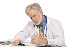 Doctor Completing Paperwork Royalty Free Stock Photos