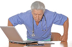 Doctor with a computer sitting on a light backgr. Caucasian doctor with a computer sitting on a light background stock photos
