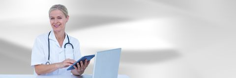 Doctor at computer with tablet against white blurred abstract background Royalty Free Stock Photos