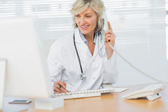 Doctor with computer using phone at medical office Stock Images