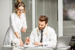 Doctor con el ayudante femenino en la oficina Fotografía de archivo libre de regalías