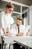 Doctor con el ayudante femenino en la oficina Imagenes de archivo