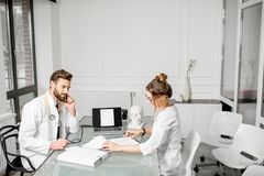 Doctor con el ayudante femenino en la oficina Foto de archivo libre de regalías