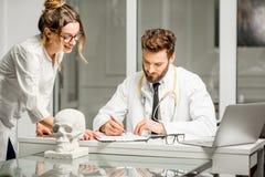 Doctor con el ayudante femenino en la oficina Foto de archivo