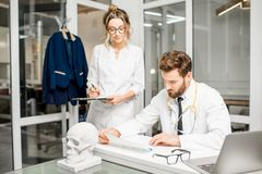 Doctor con el ayudante femenino en la oficina Imágenes de archivo libres de regalías