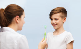 Doctor con el cepillo de dientes y el muchacho feliz en clínica Foto de archivo