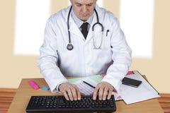 Doctor con el estetoscopio alrededor de su cuello que mecanografía encima de un informe Imágenes de archivo libres de regalías