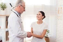 Doctor con el estetoscopio con el paciente femenino en oficina El doctor es mujer confortante imagenes de archivo