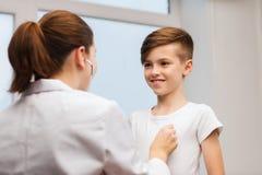 Doctor con el estetoscopio que escucha el niño feliz Imagen de archivo libre de regalías