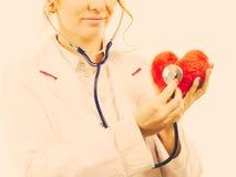 Doctor con el estetoscopio que examina el corazón rojo Fotografía de archivo libre de regalías