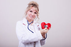 Doctor con el estetoscopio que examina el corazón rojo Imagen de archivo libre de regalías