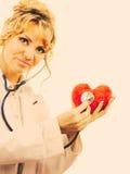 Doctor con el estetoscopio que examina el corazón rojo Fotografía de archivo