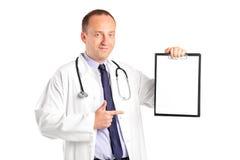 Doctor con el estetoscopio que señala en un sujetapapeles Imágenes de archivo libres de regalías