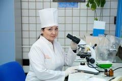 Doctor con el microscopio en laboratorio Fotos de archivo