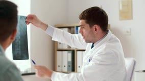 Doctor con el paciente de la radiografía y del varón en el hospital metrajes