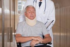 Doctor con el paciente en silla de ruedas Fotos de archivo