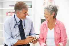 Doctor con el paciente femenino imagenes de archivo