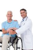 Doctor con el paciente mayor en silla de ruedas Fotos de archivo libres de regalías