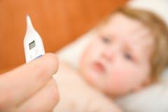 Doctor con el termómetro del bebé y de la lectura Fotos de archivo libres de regalías