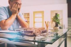 Doctor con exceso de trabajo en su oficina Imágenes de archivo libres de regalías