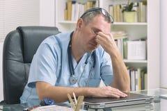 Doctor con exceso de trabajo en su oficina Foto de archivo libre de regalías