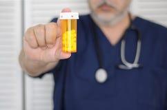Doctor con la botella de píldora foto de archivo