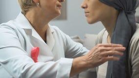 Doctor con la cinta rosada que conforta al enfermo de cáncer del pecho, ayuda psicológica metrajes