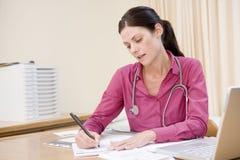 Doctor con la escritura de la computadora portátil en la oficina del doctor Imagen de archivo libre de regalías