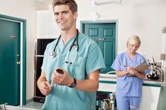 Doctor con la jeringuilla mientras que enfermera que toma abajo de informe fotos de archivo libres de regalías