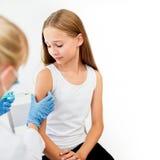 Doctor con la jeringuilla que hace la inyección a la muchacha Imagenes de archivo