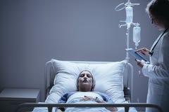 Doctor con la tableta al lado de la cama con la mujer mayor de muerte con la poder foto de archivo libre de regalías