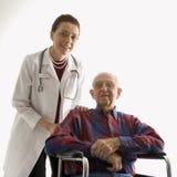 Doctor con las manos en el hombro del hombre mayor en sillón de ruedas. Fotos de archivo libres de regalías