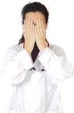 Doctor con las manos en la cara fotos de archivo libres de regalías