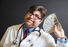 Doctor con las porciones de efectivo Imagenes de archivo