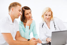 Doctor con los pacientes que miran el ordenador portátil Foto de archivo libre de regalías