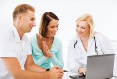 Doctor con los pacientes que miran el ordenador portátil Fotos de archivo
