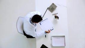 Doctor con los papeles que invita al teléfono en la clínica almacen de metraje de vídeo
