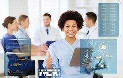 Doctor con PC de la tableta en la clínica que muestra los pulgares para arriba Fotos de archivo libres de regalías