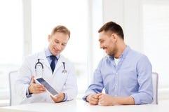 Doctor con PC y el paciente de la tableta en hospital Fotografía de archivo