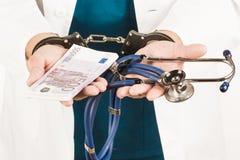 Doctor con un estetoscopio y euro-billetes de banco y esposas Crim Fotos de archivo libres de regalías